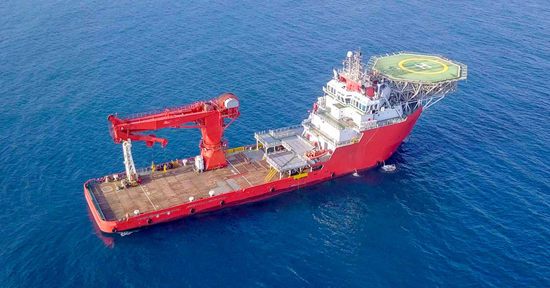 Aerial image of a medium-size red offshore supply ship with a helipad and a large crane
