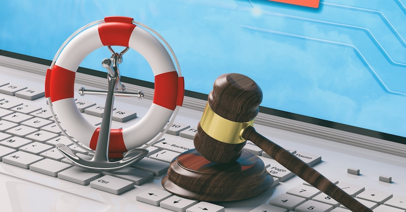 Buoy, anchor, and gavel on the keyboard of a laptop computer indicative of maritime law.