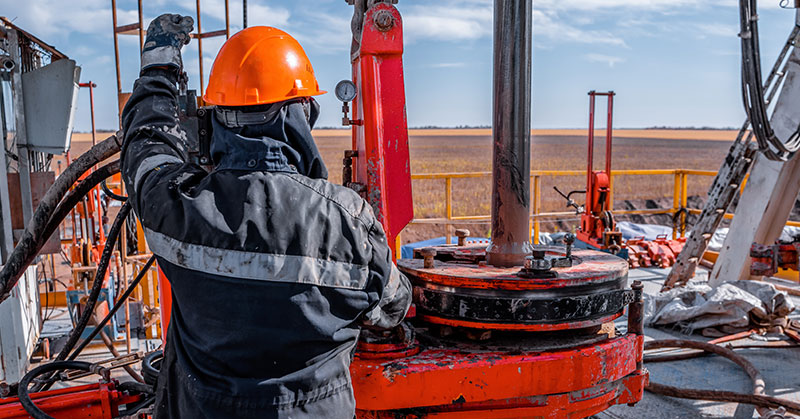 Work driller uses a hydraulic wrench to screw drill pipes to lower them into an oil well and continue drilling it.